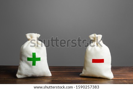 Two bags with green plus red minus. Summary and balance sheet. Income and expenses. Trade balance budgeting. Financial management, profit, losses. Risk planning. Advantages and disadvantages. Photo stock ©