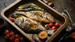 Two baked dorado fish with asparagus and vegetables in a metal tray. Top view. Free copy space. On a black stone background.