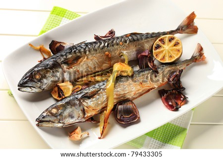 Two baked mackerel and vegetables on a platter