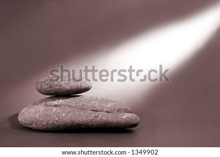Two balanced pebbles with a bean of light shining on them