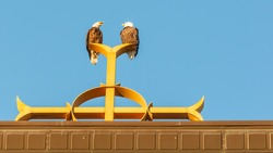 Two bald eagles on Catholic church steeple on top of the Christian cross at Annunciation Church in South Minneapolis