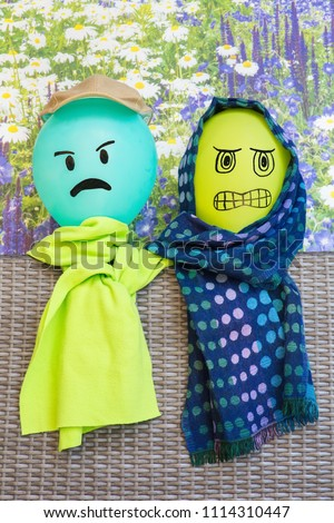 Two balloons with angry facial expression wearing green shawls #1114310447