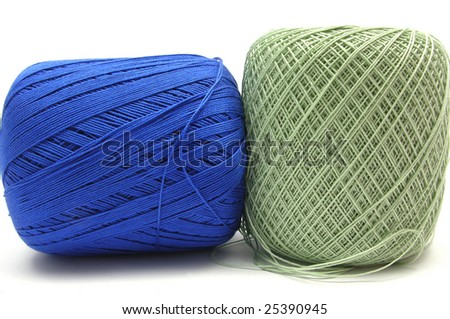Two balls of wool  in blue and green on white
