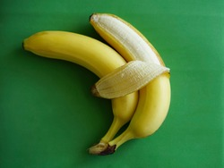 two bananas isolated on green background. Love and tenderness. sign, symbol, concept of embracing couple