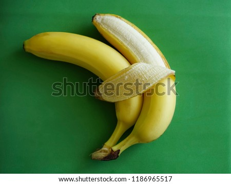 two bananas isolated on green background. Love and tenderness. sign, symbol, concept of embracing couple #1186965517