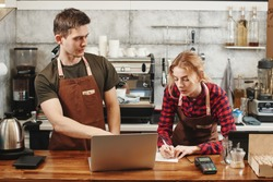Two Barista boy and girl looking at laptop in a coffee shop. Training Intern