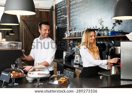 Two baristas preparing coffee at coffee-shop
