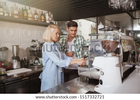 Two baristas working at the coffee shop. Handsome male barista teaching new employee using coffee machine. Cafe, profession, employment concept