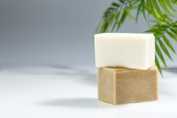 Two bars of white and brown natural dish washing solid soap with palm leaves on the background. Copy space for text