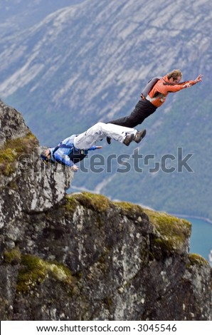 Two BASE jumpers jumping off a big cliff in Norway one doing a back flip (gainer)