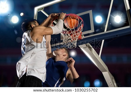 Two basketball players in action in gym