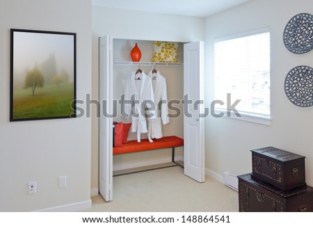 Two bathrobes hanging on a racks  and shelve with some decorations as vase and pillow in the closet. Interior design.