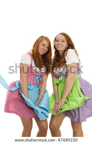 two bavarian dressed girls fighting with wind on white background