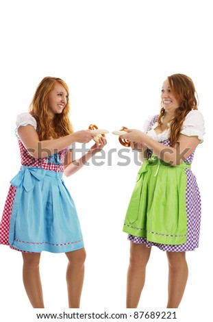 two bavarian dressed girls pulling on veal sausages on white background