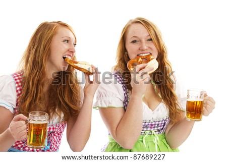 two bavarian women eating pretzels and holding beer on white background