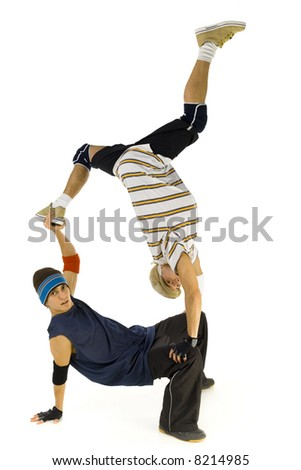 Two bboys doing some kind of exercise. One is standing on hands on other's knee. They are looking at camera. Isolated on white in studio. Side view, whole body