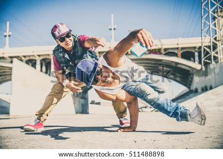 Two bboys doing some stunts - Street artist breakdancer taking an acrobatic selfie outdoors