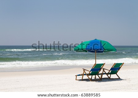Two beach chairs and an umbrella sit on the sand at Fort Walton Beach, Florida. - stock photo