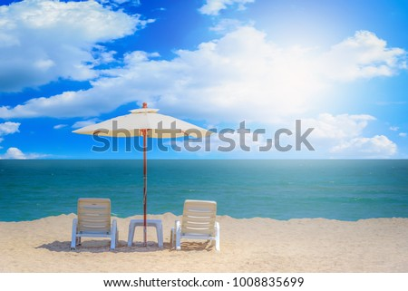 Two beach chairs and white umbrella with blue sky background on the tropical beach at daytime #1008835699