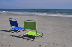 Two beach chairs in the sand.