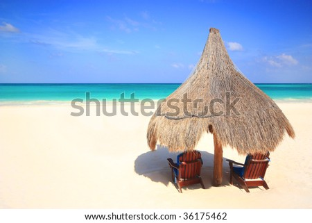 Two beach chairs under the shade of a grass umbrella overlooking a stunning tourist resort beach