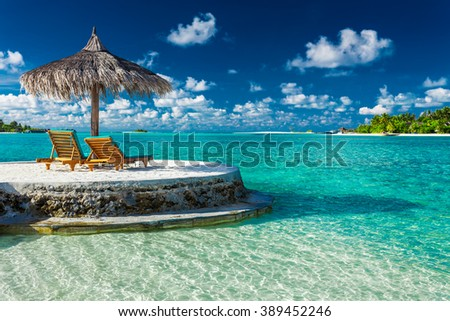 Two beach chairs under umbrella with ocean view in tropical Maldives #389452246
