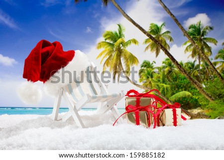 two beach chairs with santa hat and christmas gifts in snow before tropical background