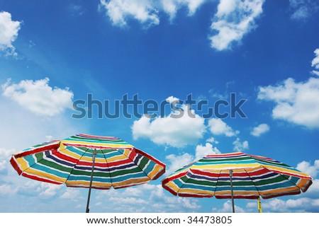 Two beach umbrella and blue cloudy sky