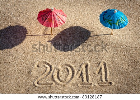 Two Beach Umbrellas are standing in the Sand. New year 2011 at the beach!