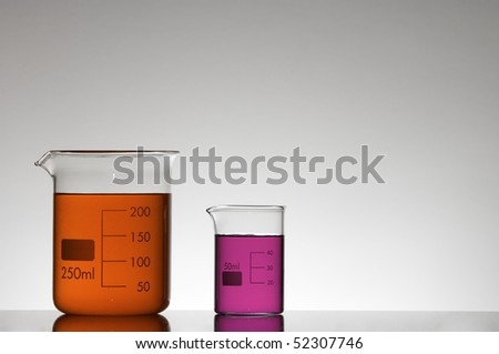 two beakers with red and pink liquid
