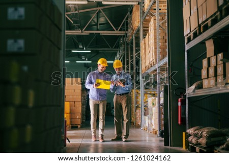 Two bearded businessmen with helmets on head comparing documents while standing in warehouse.