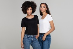 Two beautiful african american girls posing in studio in jeans and casual basic tshirts, looking and smiling to the camera.