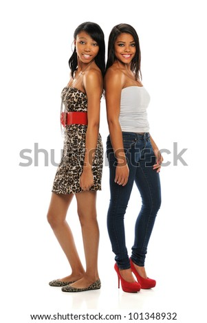 Two beautiful African American women standing side by side isolated over white background