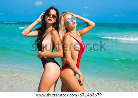 Two beautiful amazing tanned sexy girls, on the beach, blonde and brunette, long hair, perfect sports figures, trendy red and black swimsuits, sunglasses, relaxation on a tropical island, summer