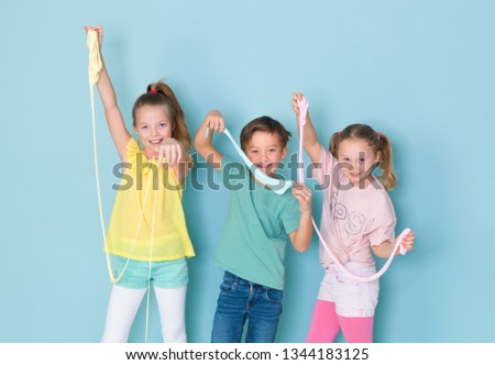 two beautiful and funny girls and one cool boy playing with a lot of slime in front of blue background and having a lot of fun