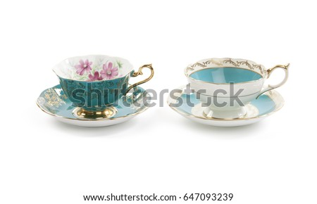 Two beautiful antique tea cups with saucers isolated on a white background.