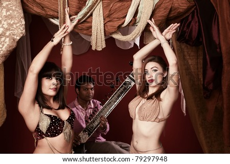 Two beautiful Arab belly dancers with Indian man playing Sitar