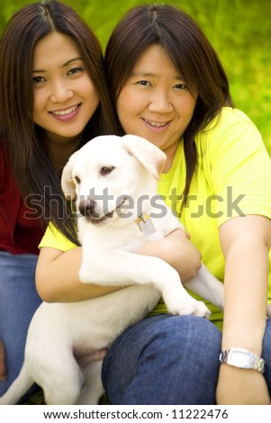 two beautiful asian women holding a labrador dog in a park