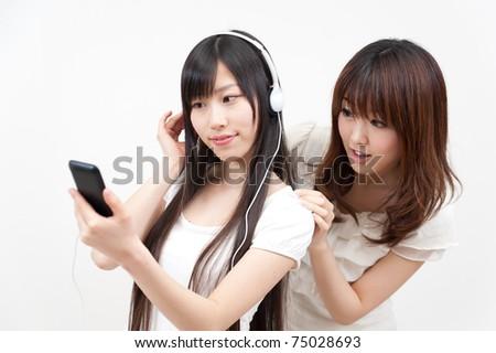 two beautiful asian women listening to music