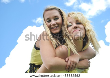 Two beautiful, attractive, happy, carefree blond teenage girls giving each other a piggyback ride in the sunshine with clouds over a blue sky in the background.