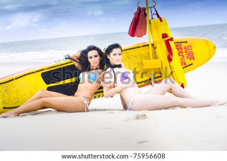 Two Beautiful Bikini Clad Women Sitting Back To Back Together Next To A Yellow Surf Rescue Board And Ocean Safety Floats In A Dynamic And Hot Beach Portrait