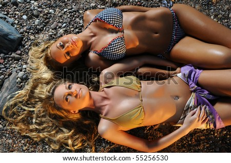 Two beautiful blond girls lying on the beach