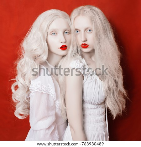 Stock Photo Two beautiful blonde girls with long white hair in white dresses on a crane background
