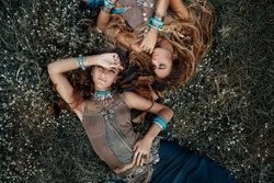 Two beautiful boho girls in ethnic jewelry outdoors. Top view