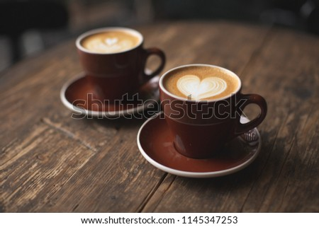 Two beautiful burgundy cups of cappuccino with trendy heart shape latte art. Summer loft cafe background. Urban space. Drinking coffee on the terrace.