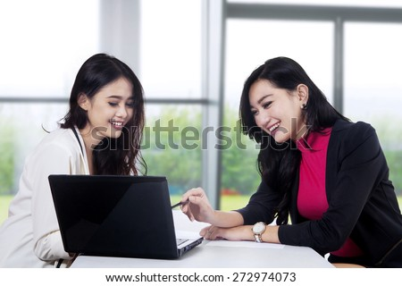 Two beautiful businesswoman office worker discussing in the office