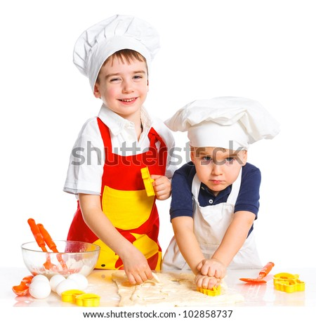 Two beautiful caucasian brothers making a cake, smiling happily, isolated on white background