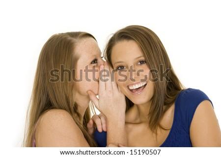 Two beautiful caucasian women telling secret on a white background