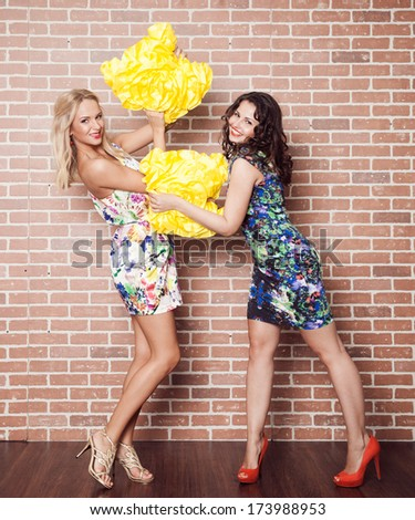 Two beautiful cheerful young girlfriend pillow fight on brick background