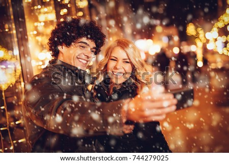 Two beautiful cheerful young people taking selfie in the street with snowflakes surrounding.  #744279025